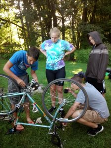 Learning how to fix bicycles on a Teen Treks summer bike tour while drinking coffee.